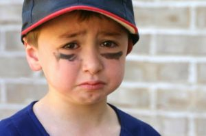 little boy in baseball cap with look of sadness and disappointment