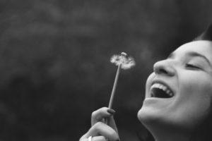 happy, optimistic woman blowing dandelion