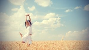 woman jumping for joy, representing living a happy life