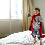 Boy playing superhero.