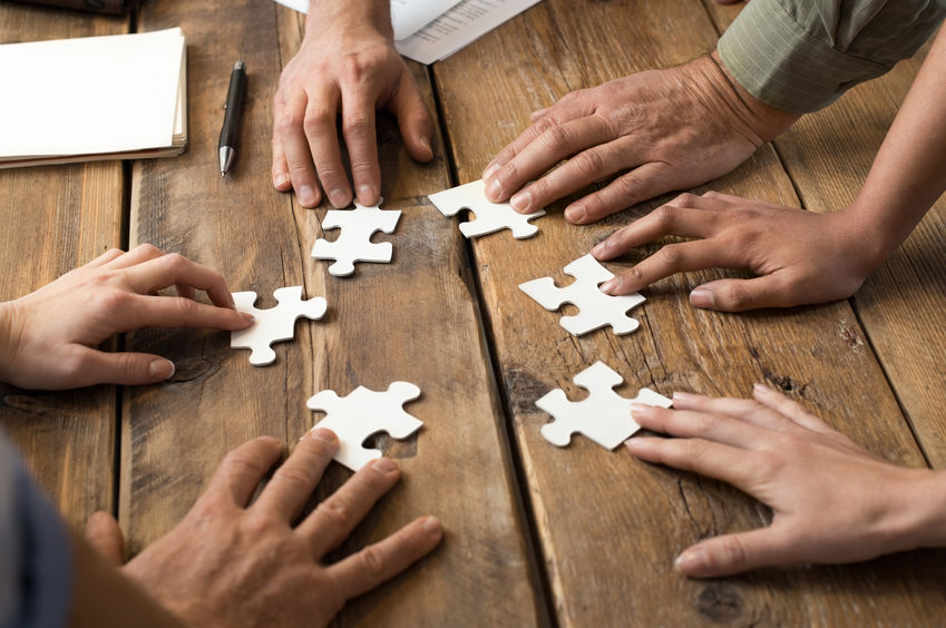 business men and women trying to solve a puzzle by collaborating