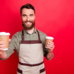 portrait of man offering latte to friend