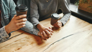 Couple holding hands, showing unity and love as they sip coffee.