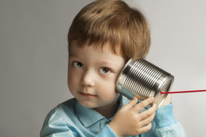 small boy listening through tin can