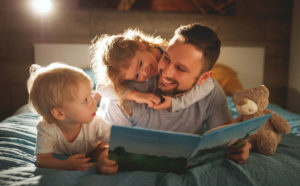 Father reading story to children before going to bed