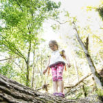 Young girl standing on a log, facing her fear