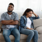 couple seated on couch using poor listening skills