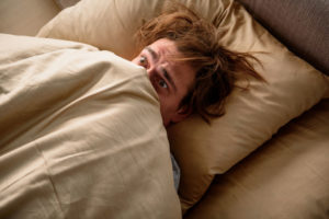 scared male lying in bed with covers pulled up to face
