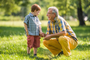 Grandfather listening to grandson in park
